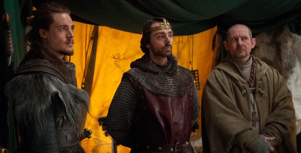 El padre Beocca (derecha) mediará entre Uhtred (izquierda) y el rey Alfredo (centro), pero siempre poniendo su fe por encima de todo.
